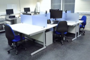 A cluster of light grey topped crescent workstations with light blue acrylic desk top dividing screeens - King's Lynn, Norfolk