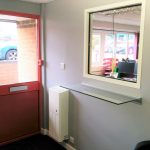 Reception refurbishment with new UPVC front doors, cladding and new hatch signing in area.